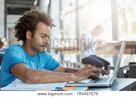 Stylish Afro American Student Keyboarding On Laptop Computer While Sitting At Cafe Table With Textbo