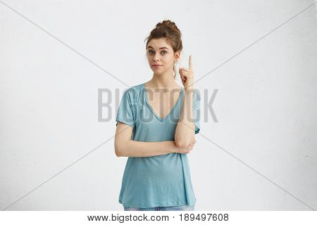 I Have A Great Idea! Smart Quick-witted Pretty Girl With Hair Bun Keeping Finger Pointed Upwards. Cu