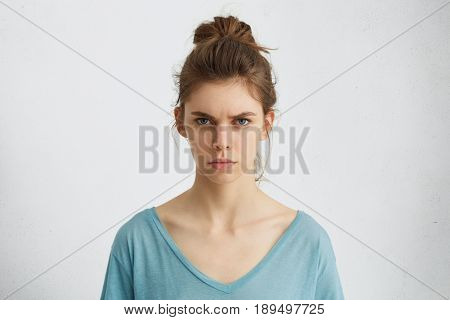 Portrait Of Outraged Young Woman With Oval Face, Blue Eyes And Hair Bun Wearing Blue Casual Sweater