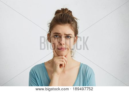 Young Woman With Fair Hair And Blue Eyes Frowning Her Eyebrows Holding Index Finger On Chin Having D