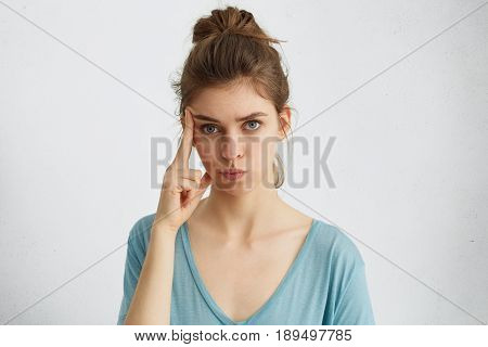 Serious Attractive Blue-eyed Woman With Hair Knot Wearing Casual Clothes Holding Finger On Her Templ