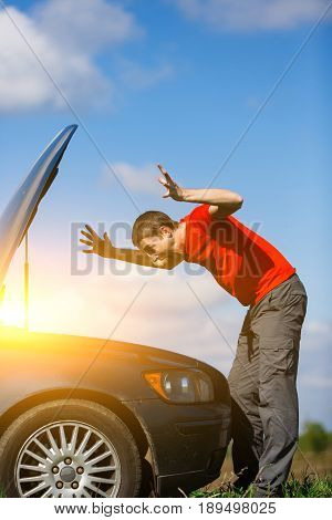 Brunet looks at car's hood on road during day