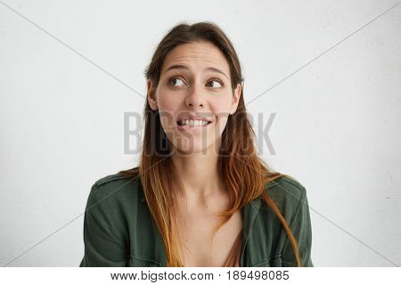 Indoor Portrait Of Shy Pleasant-looking Female Looking Embarrassed Aside Biting Her Lower Lip Wantin