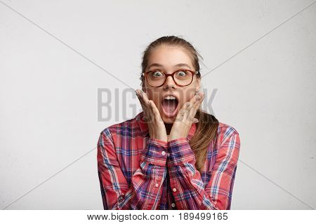 Indoor Shot Of Shocked Young Attractive Female In Big Glass Eyewear Dressed Casually Holding Hands O
