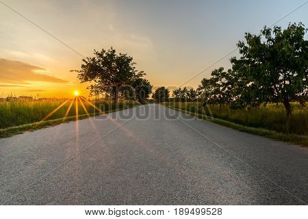 Sunset With Long Orange Beams Over The Lone Road