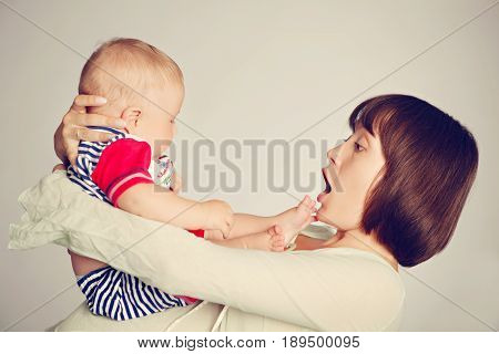 Mom is very surprised how quickly her child grew up. Opening her mouth she holds her son in her arms and looks at him.