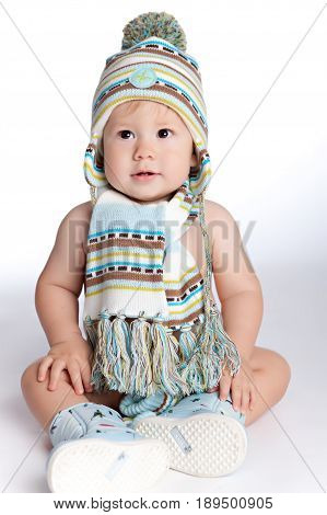 Kid dressed in winter hat scarf and boots sitting on the floor on a clean white background