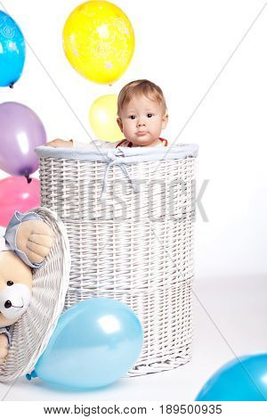 The child climbed into a white wicker laundry basket which is surrounded by colorful balloons and peeps showing his head