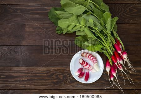A bunch of radish and cut radish on a white plate.
