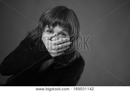 The girl can not help laughing and closes her mouth with her hands. Her eyes glow with unrestrained joy. Black and white picture