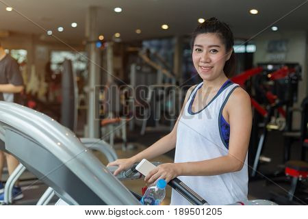 Beautiful Portrait Asian Woman Jogging And Running On Treadmill Cardio Machine In Fitness Gym Exerci