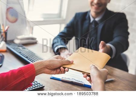 Businessman receiving envelope (money) from a woman while making contract - bribery concept