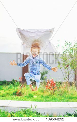 The boy jumps on the mattress lying on the grass. He floats in the air in a lotus position and above his head hangs a pillow