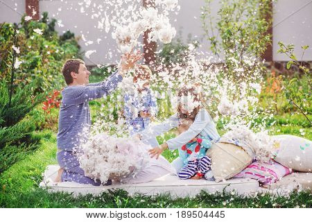A family of four members arranged a fight on the pillows. Mom Dad son and daughter fight with pillows and feathers fly around