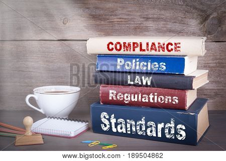 Compliance concept. Stack of books on wooden desk.