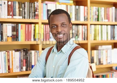 Black College Student Wearing Elegant Shirt Holding Rucksack Isolated Over Library Background Lookin