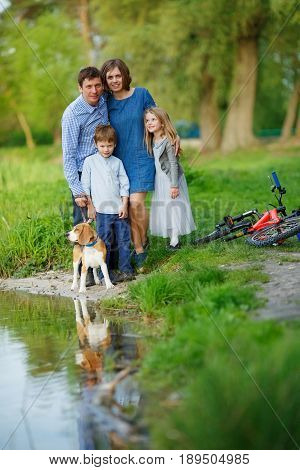 A full family is resting on the shore of a quiet lake. Mom Dad son daughter and their dog are standing by the water