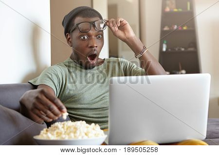 Horrified Afro American Man Dressed Casually Sitting At Home Watching Horror Films On Computer Eatti