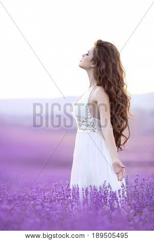 Enjoyment. Beautiful carefree brunette open arms in lavender field. Young woman portrait. Attractive girl with long curly hair style in white dress dreaming and enjoying life.