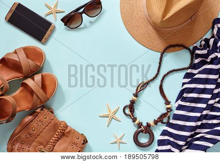 Summer sea background and women's beach accessories: straw hat, bracelets, leather sandals, glasses, beads, leather bag and striped dress, phone samsung 7 Edge. Copy space. Flat lay.