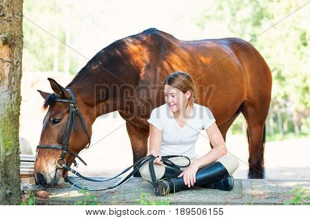 Young teenage girl equestrian sitting close to her chestnut horse. Vibrant multicolored summertime outdoors horizontal image.