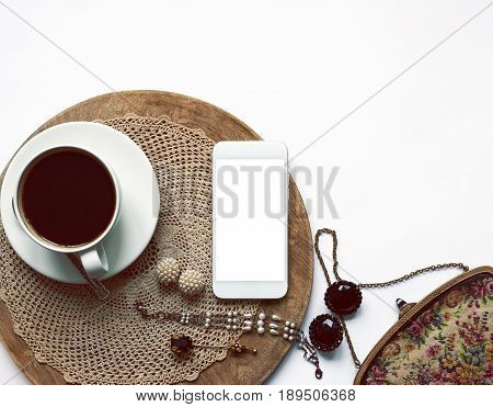Top view on a mobile phone with blank copy space screen on the white table cup of coffee vintage jewelry and accessories. Fashion designer's or stylist workspace. Mock up flat lay. Toned image