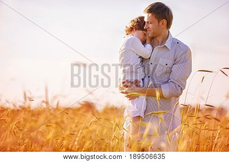 A man is holding his son in his arms standing in the middle of a wheat field. The son gently laid his head on his father's shoulder hugging him
