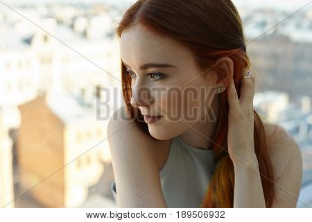Close up portrait of pretty Caucasian teenage woman looking forward at sunset in big city. Side view of pretty student female touching her colored strands of hair having pensive facial expressions