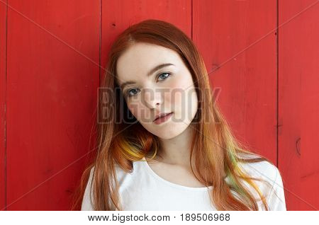 Close up portrait of pretty mixed race teenage girl looking thoughtful and dreamy at camera. Gorgeus redhead student female with colored strands of hair and green eyes standing on red wall background