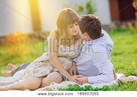 Romantic rendezvous of a young couple on a picnic. A woman in a light summer dress prepares to kiss her lover.