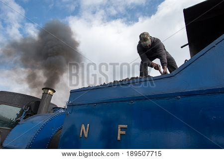 DARJEELING INDIA - NOVEMBER 27 2016: technician services the steam engine hauled DHR Toy Train used for joy ride tours as well as regular transport services in Darjeeling.