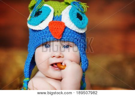 A small boy dressed in a homemade knitted cap in the shape of an owl gnaws a bagel