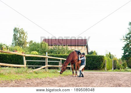 Young girl equestrian with her chestnut horse. Multicolored outdoors horizontal image.