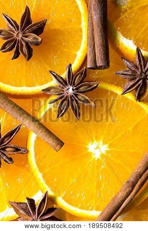 bright orange background from slices of juicy oranges with anise stars cinammon