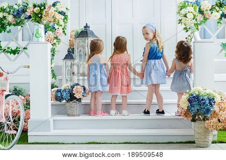 A small fashion girl imitating adults met her friends on the porch and escorted her into the house looking back.