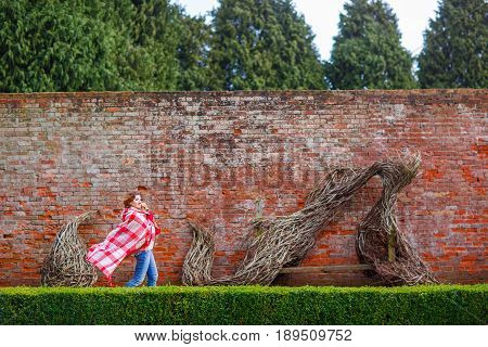A woman with a dog in her hands runs along an old high brick wall. Plaid flying in the wind behind her