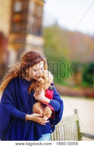 The girl in a blue cape gently hugs her little dog rejoicing at the long-awaited meeting with the pet. She closed her eyes and pressed the poodle to her face