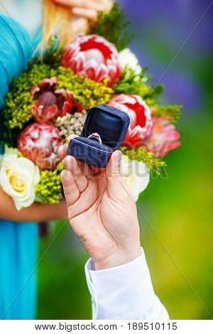 A man's hand stretches a box with an engagement ring to a beloved woman offering her to marry. She stands in the middle of a lavender field holding a lush bouquet of flowers in her hands