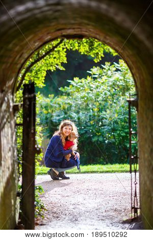 The woman crouched next to the old stone arch in the English garden and holds a small red poodle