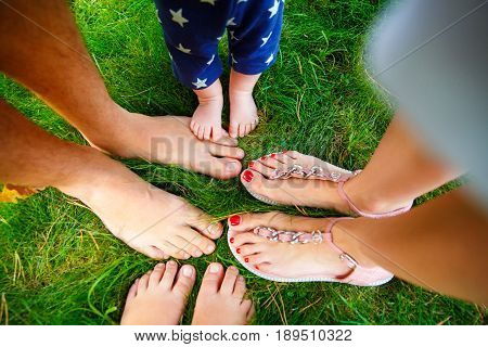 Bare feet of a family of four standing on green grass facing each other