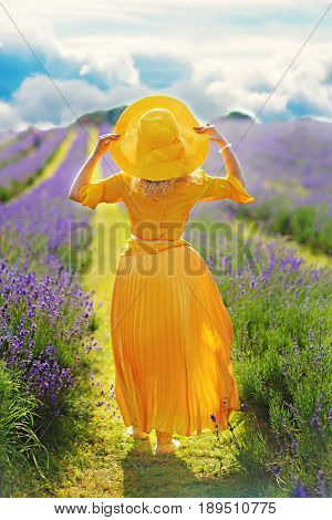 Woman in yellow dress and hat on the field in the rays of sunset