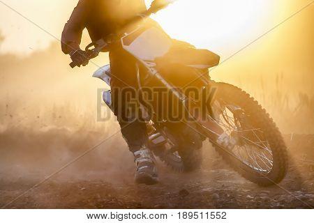 Silhouette motocross race speed in dirt track.