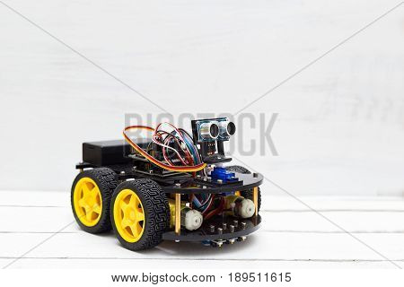 Robot on four yellow wheels on a light background