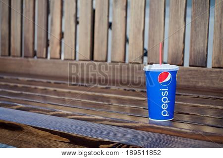 Minsk, Belarus, may 19, 2017: paper cup of Pepsi on a bench in the city. Pepsi is a carbonated soft drink produced PepsiCo