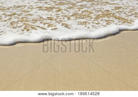 white foam of a sea wave gently moving over the wet sand at low tide