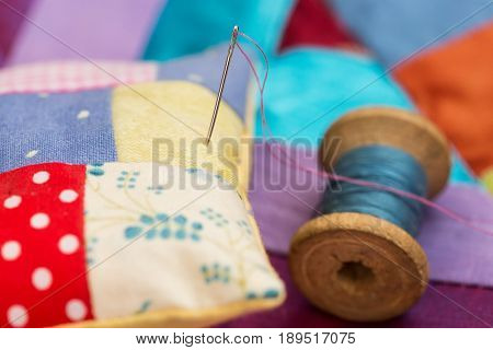 patchwork, quilting, sewing, tailoring and fashion concept - close-up beautiful colorful stitched cushion and needle, macro on pillow with background of blue, lilac and red flaps of fabric