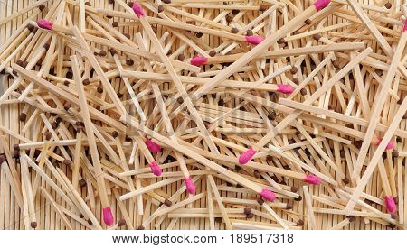 Many matches with brown and rose match heads scattering on three rows of matches