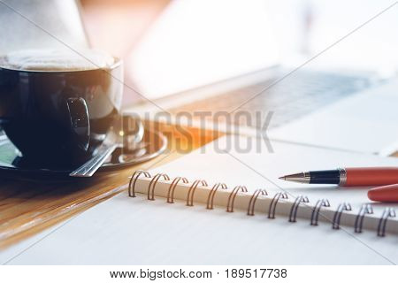 Close up Wooden Table of Businessman with Notebook and Pen Laptop Computer Mobile Phone and A Cup of Coffee to Stay as Stress Reliever.