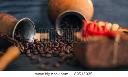 Coffee beans scattering off big and small copper coffee pots and red hot chili peppers on black slate surface