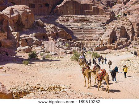 Petra Jordan - 9 March 2017: Tourists walking near ruins of roman amphitheatre Petra Jordan 9 March 2017